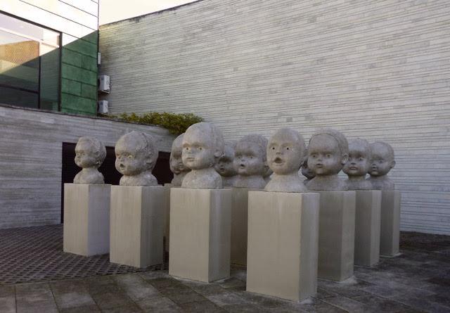 Samling av uttrycksfulla barnhuvuden vid museets entré