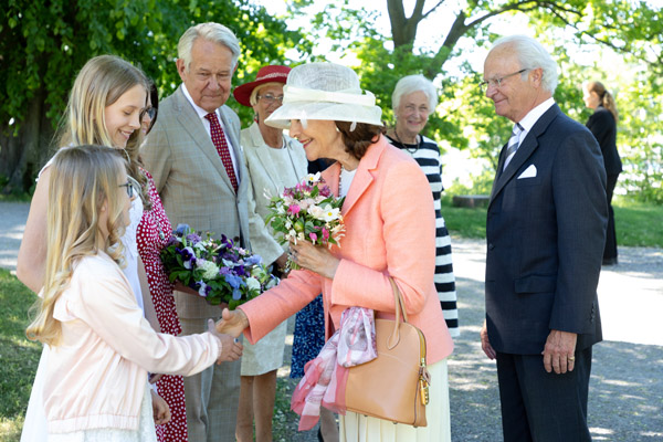 Flickorna Idun och Säva överlämnar blommor till Drottningen